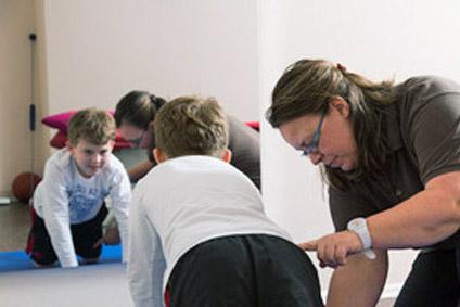 Physiotherapeutin trainiert mit Kind